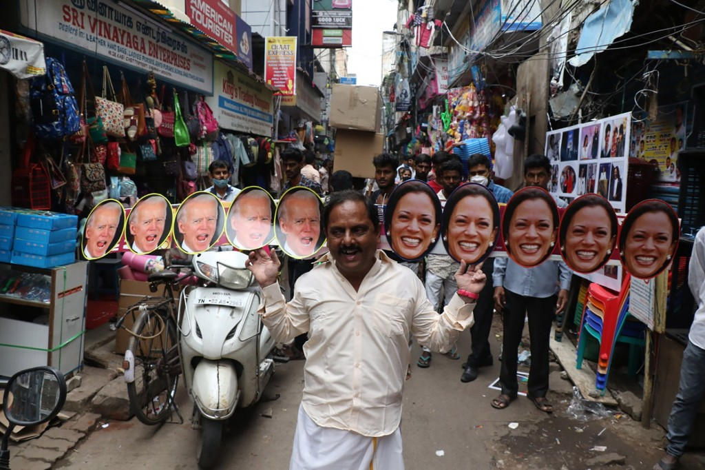 A man wears cut-outs of U.S.President-elect Joe Biden and Vice President-elect Kamala Harris and walks on a street in Chennai, India, Wednesday, Jan. ...