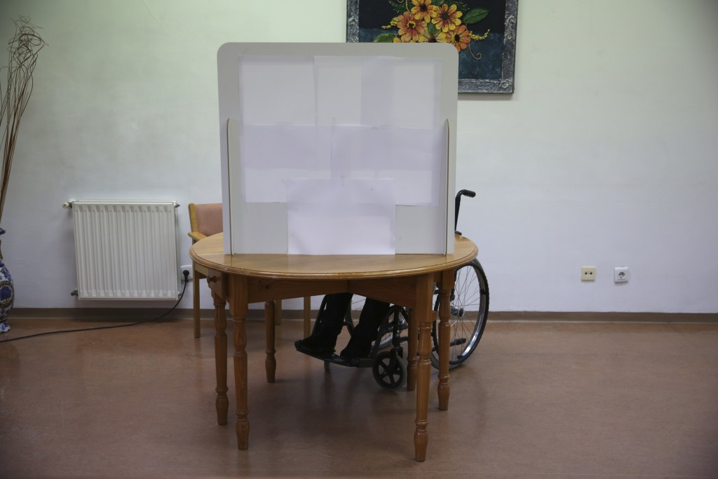 Olivia Bibe, 87, marks her presidential election ballot behind a makeshift voting booth at the elderly care home where she resides in Montijo, south o...