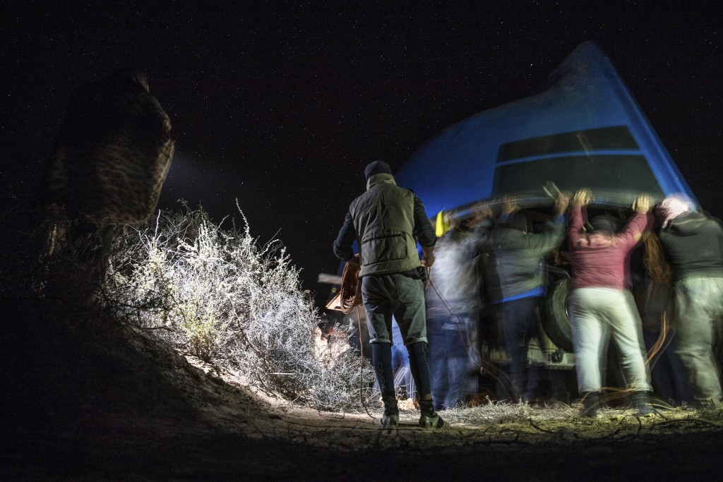 Smugglers lift onto a vehicle a fishing boat intended to be used to transport migrants to the Canary Islands, in a remote desert out of the town of Da...