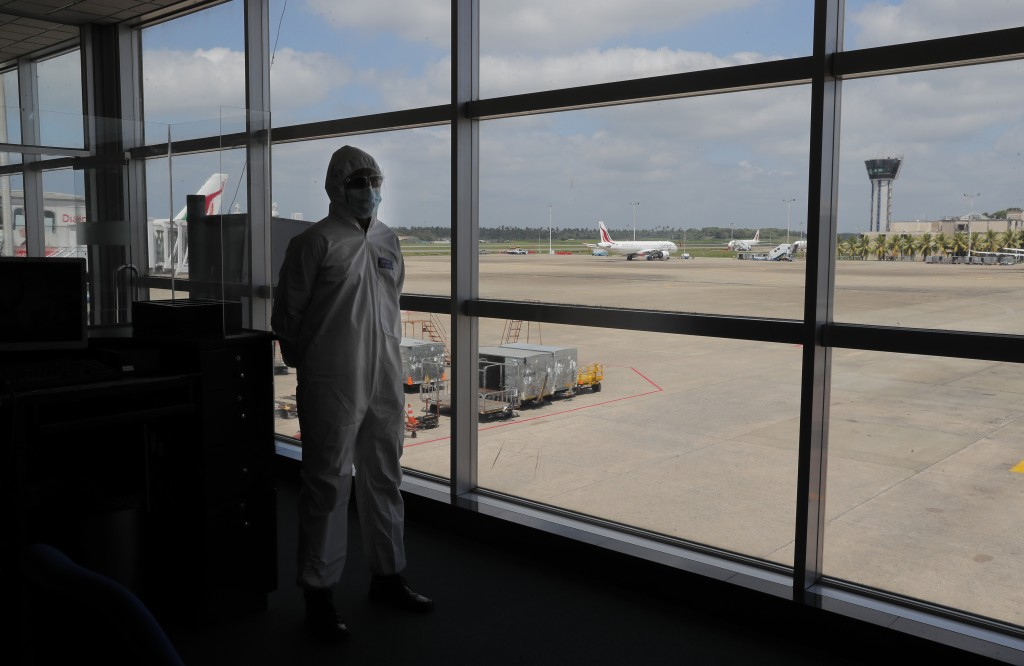 A Sri Lankan airport worker in protective suit stands inside a terminal at the Katunayake International Airport in Colombo, Sri Lanka, Wednesday, Jan....