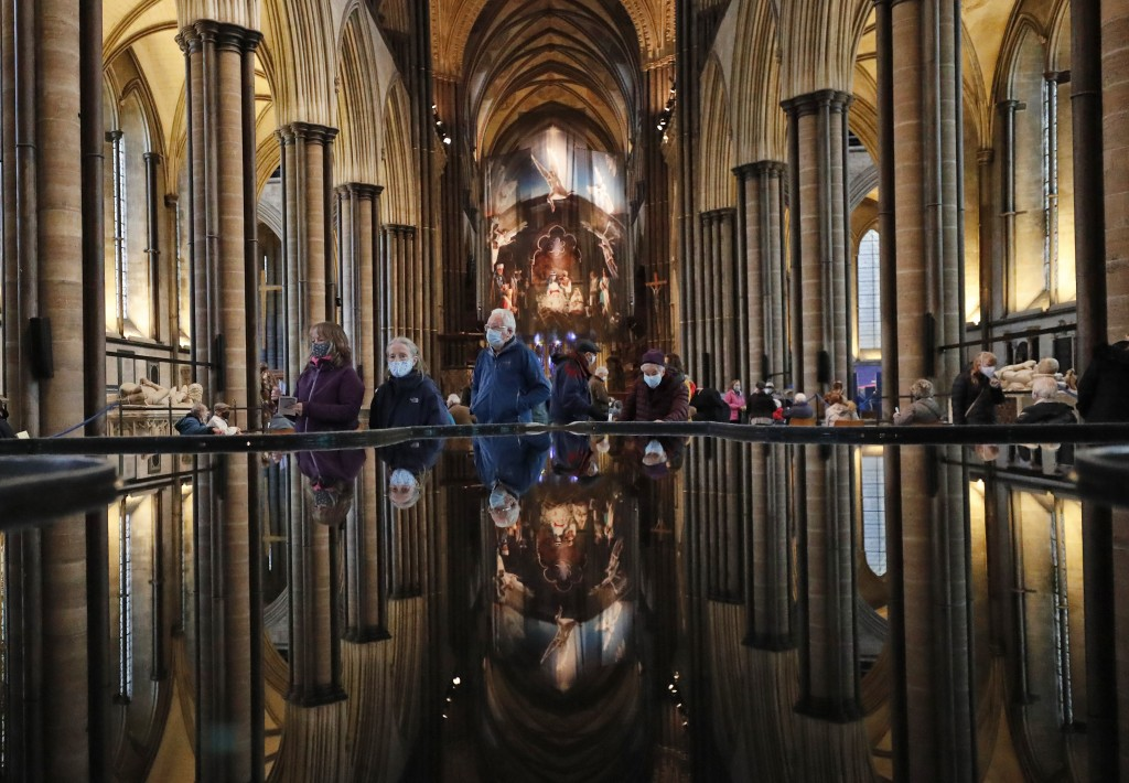 People are reflected in the 'Refection Pool' inside Salisbury Cathedral in Salisbury, England, Wednesday, Jan. 20, 2021, as they leave after receiving...