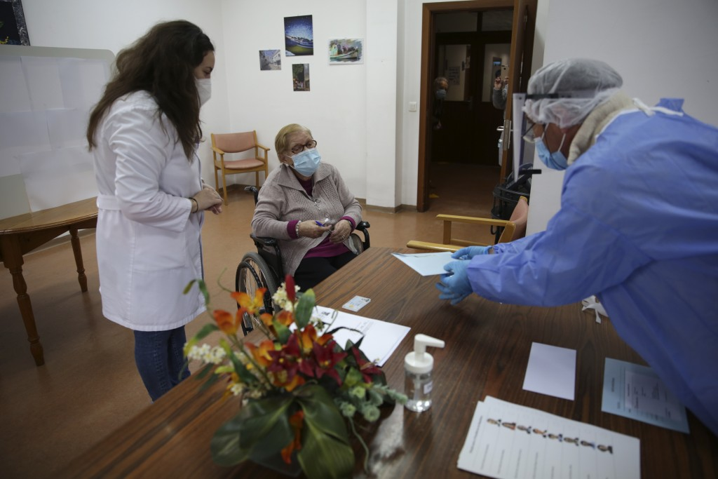 Olivia Bibe, 87, watches as municipal worker Mario Matos, right, seals an envelope with her presidential election ballot at the elderly care home wher...