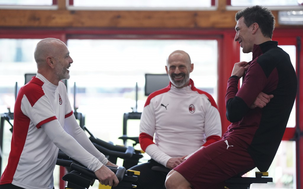 Mario Mandzukic talks with Milan coach Stefano Pioli at the Milanello Milan's sport center prior to his first training session, in Carnago, Italy, Tue...