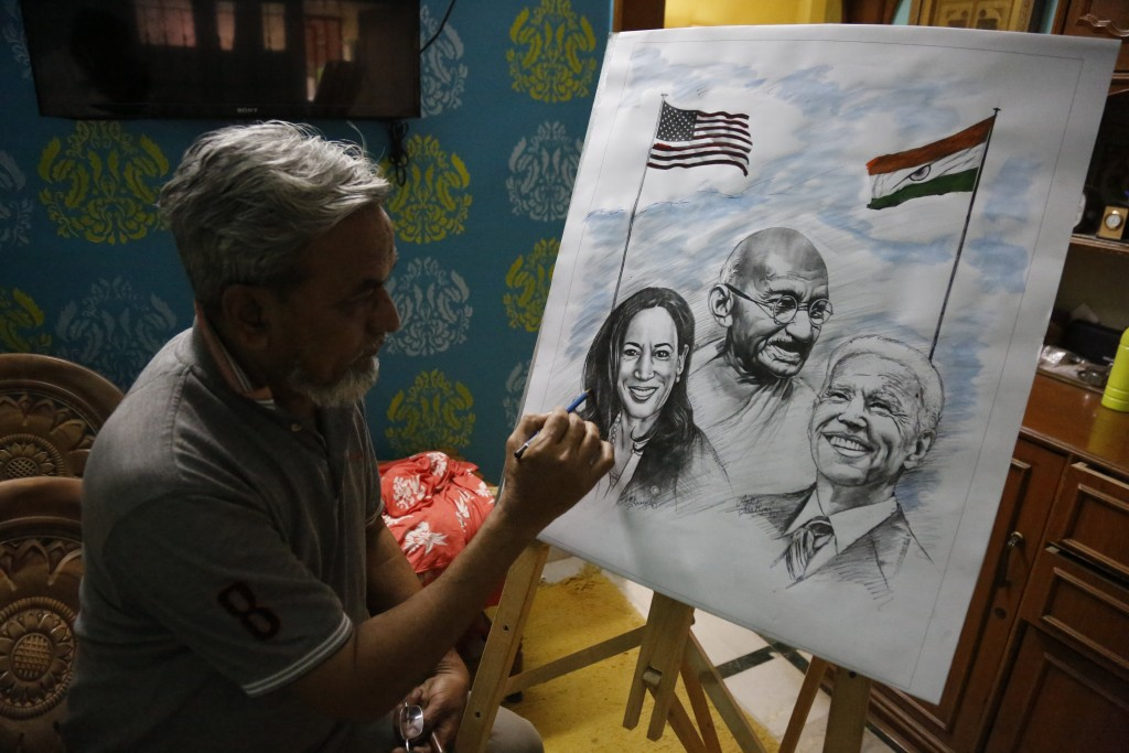 An Indian artist Aejaz Saiyed gives finishing touch to an art work featuring U.S.President-elect Joe Biden, Vice President-elect Kamala Harris  and In...