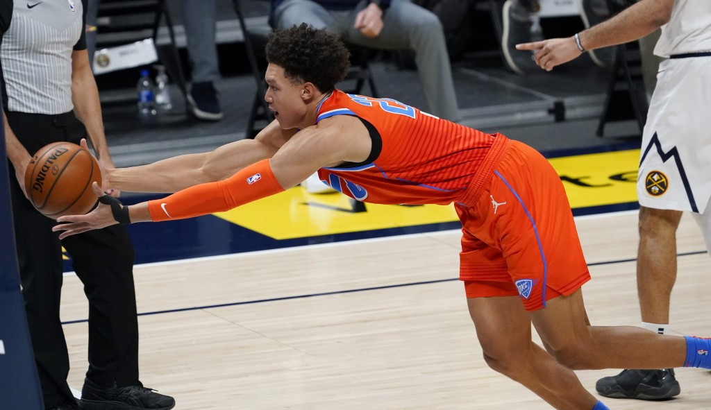Oklahoma City Thunder forward Isaiah Roby reaches out to pull in a loose ball against the Denver Nuggets in the first half of an NBA basketball game T...
