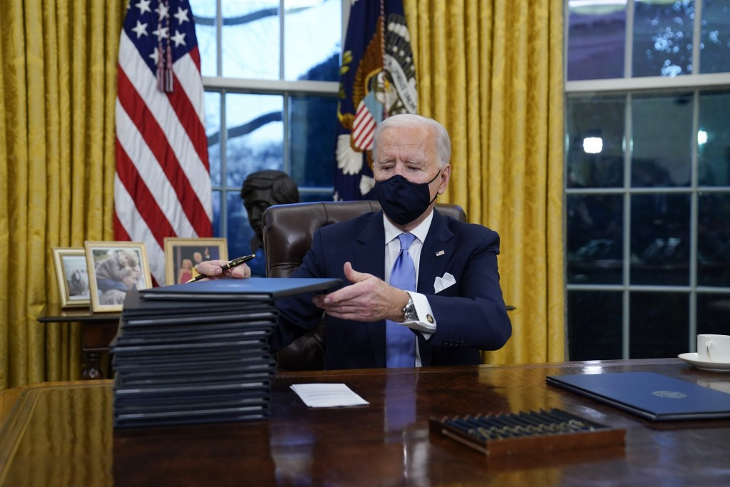 President Joe Biden signs his first executive orders in the Oval Office of the White House on Wednesday, Jan. 20, 2021, in Washington.(AP Photo/Evan ...