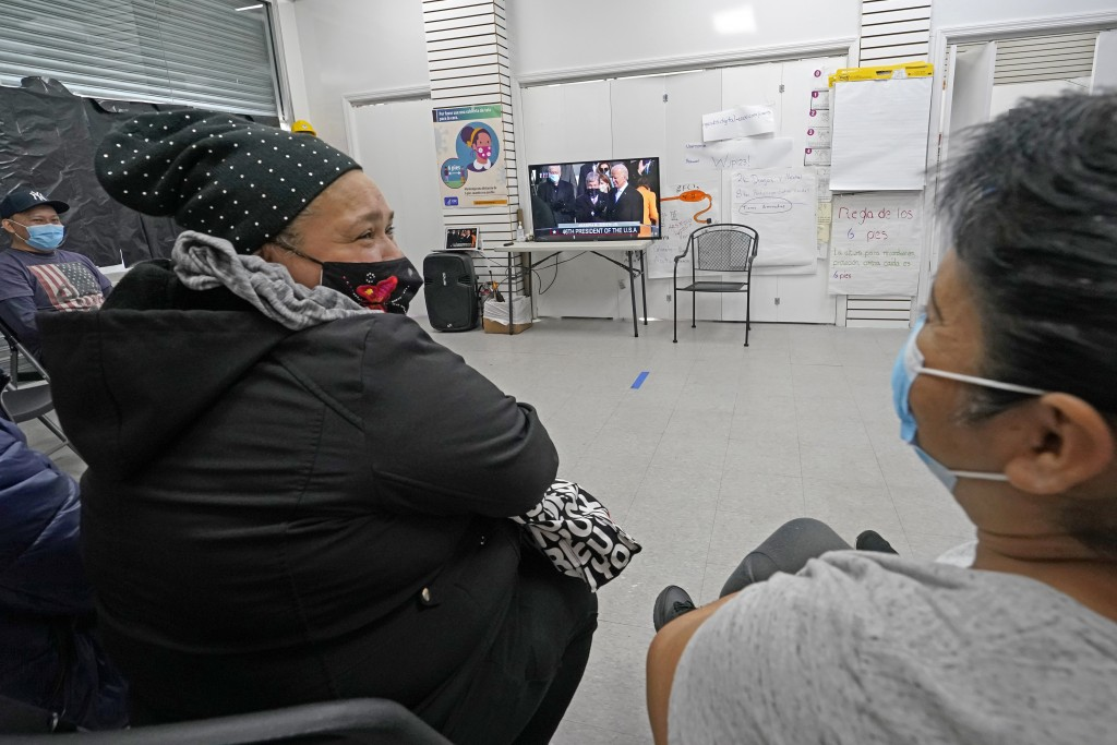 Immigrant worker Blanca Cedillos, center, who is a nanny, glances over at cleaning lady Graciela Uraga, as they watch the presidential inauguration fr...