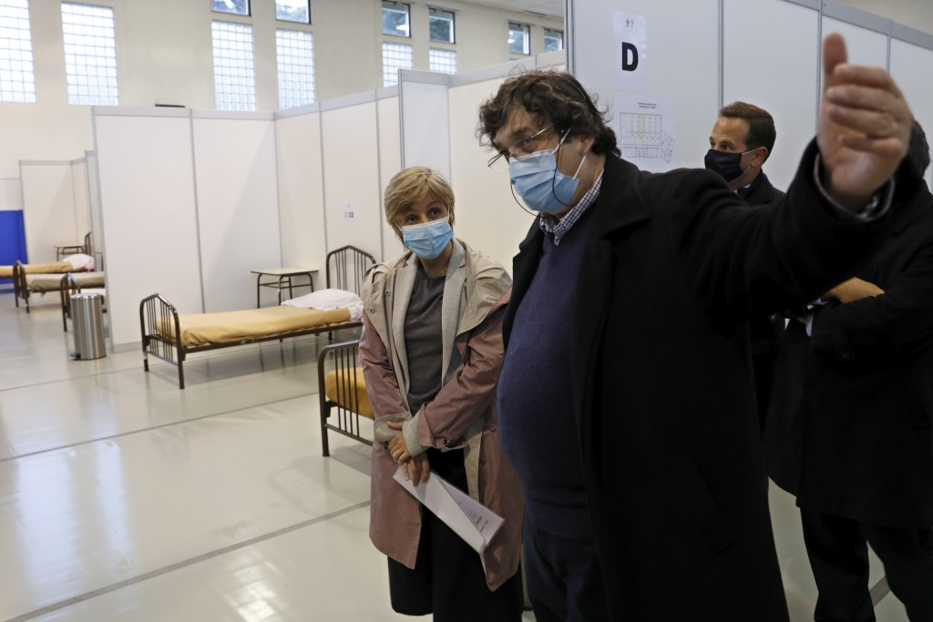 """Portuguese Health Minister Marta Temido, centre, visits a new field hospital set up in a sports hall in Lisbon, Wednesday, Jan. 20, 2021. """"The gravity..."""