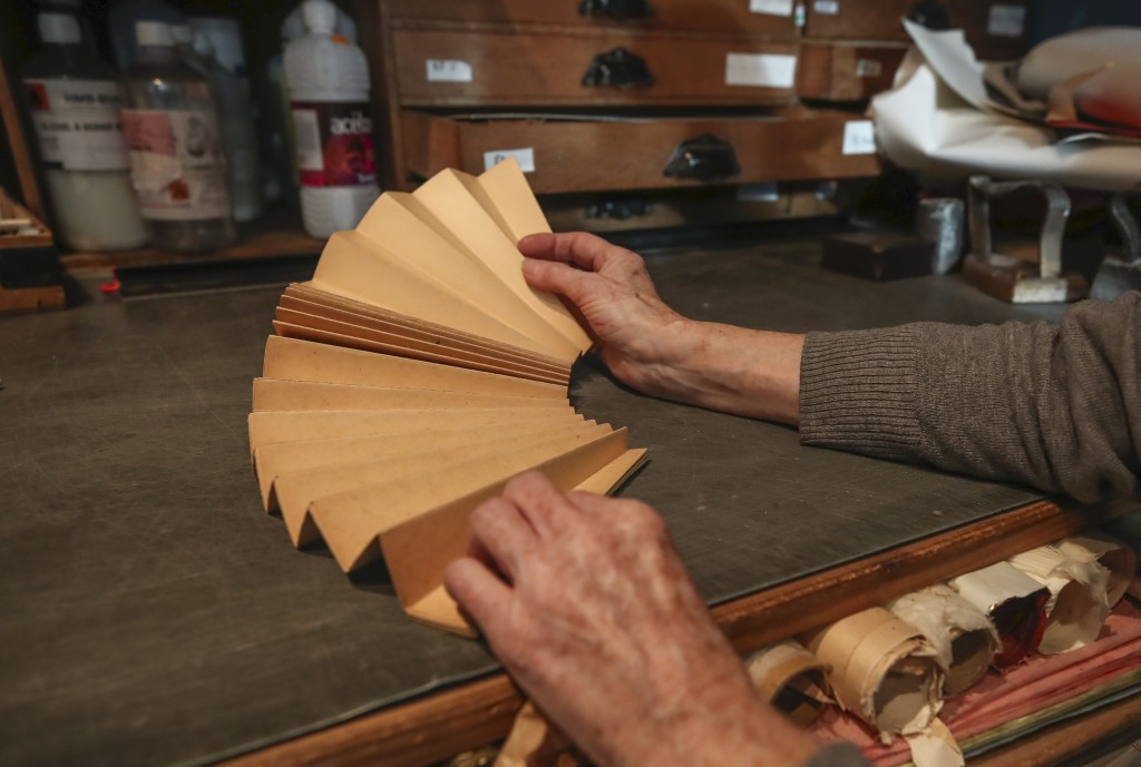 Anne Hoguet, 74, fan-maker and director of the hand fan-making museum unfolds a mounting fan in her workshop Wednesday, Jan. 20, 2021. Just like the l...