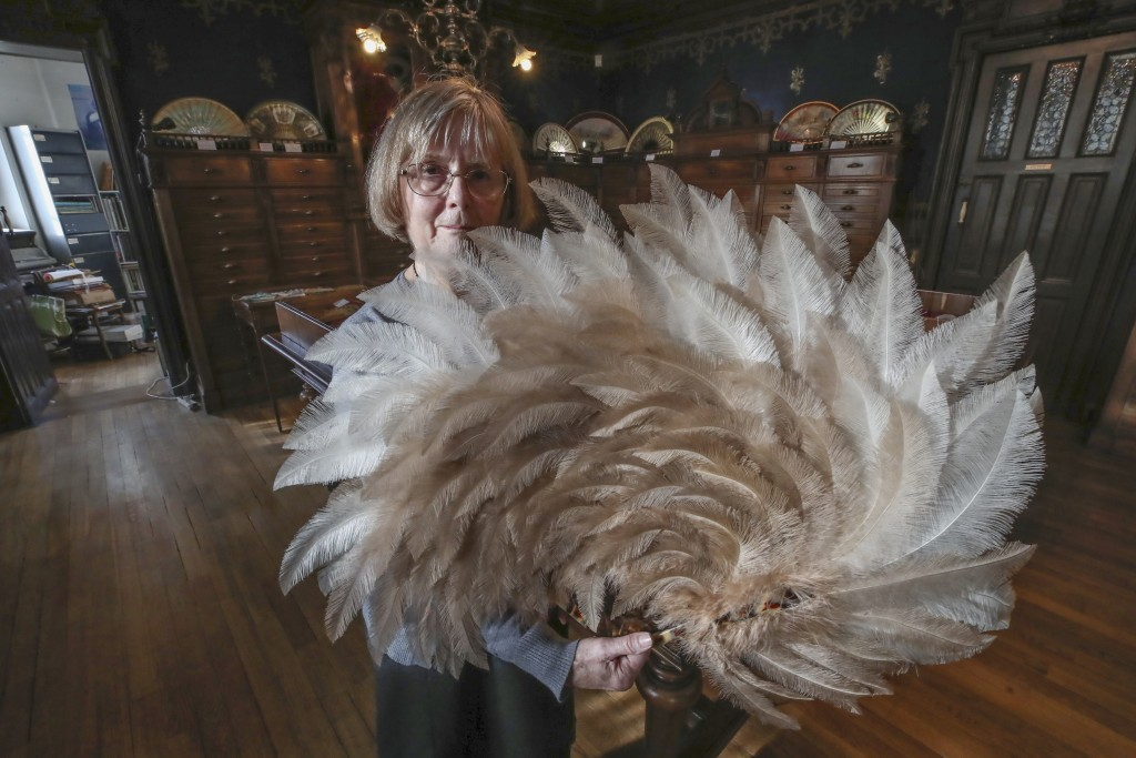 Anne Hoguet, 74, fan-maker and director of the hand fan-making museum poses with a feather fan at the museum in Paris, Wednesday, Jan. 20, 2021. Just ...