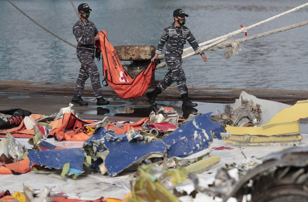 Navy sailors carry a body bag containing the recovered remains of victims of the Sriwijaya Air flight SJ-182 that crashed on Jan. 9, at Tanjung Priok ...