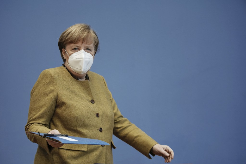 German Chancellor Angela Merkel arrives wearing a protective mask for a press conference on the current situation in Berlin, Germany, Thursday, Jan. 2...
