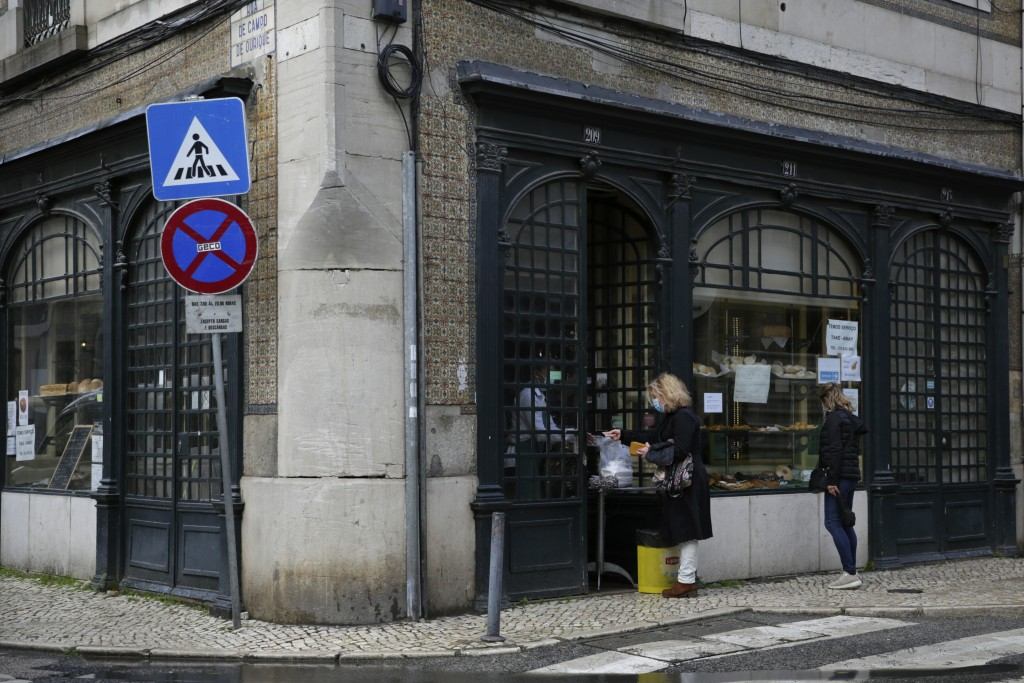 A woman buys food at the door of a pastry shop in Lisbon, Wednesday, Jan. 20, 2021. The pandemic has gained momentum in Portugal since Christmas, when...