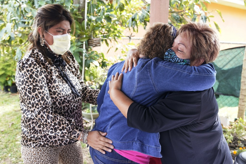 Elvira Carvajal, right, hugs Blanca Flores, as Irma Durand, left, cries after watching the swearing-in ceremony for Joe Biden as the 46th President of...