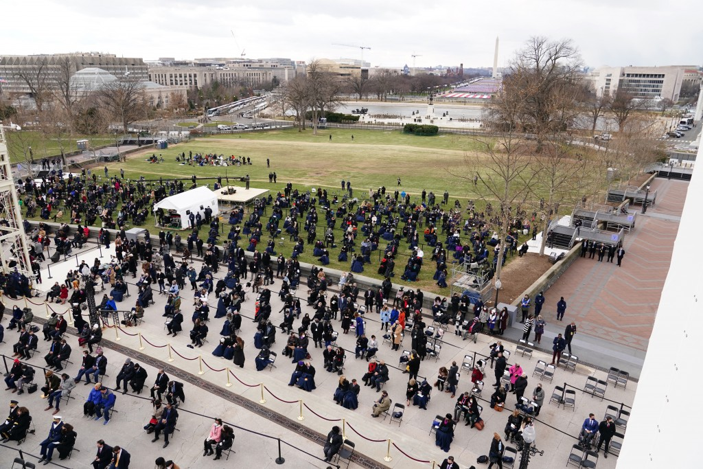Attendees sit on the West Front of the U.S. Capitol at the 59th Presidential Inauguration in Washington, Wednesday, Jan. 20, 2021. (Kevin Dietsch/Pool...