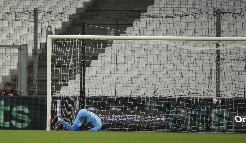 Lens' Simon Banza scores the opening goal of his team during the French League One soccer match between Marseille and Lens at the Veledrome stadium in...