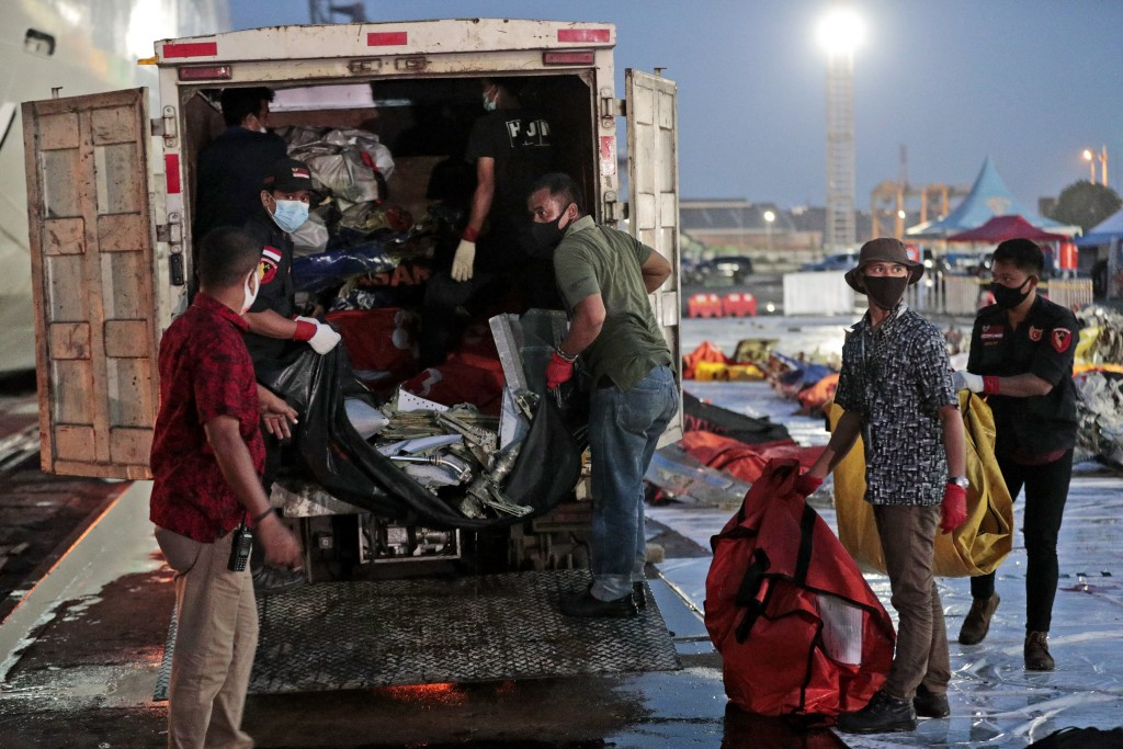Workers load wreckage from Sriwijaya Air flight SJ-182 that crashed into the Java Sea on Jan. 9, onto a truck be transported for further investigation...