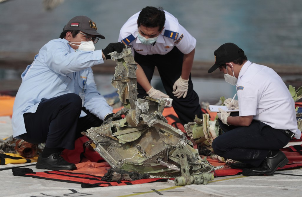 Investigators inspect a pieces of the Sriwijaya Air flight SJ-182 retrieved from the Java Sea where the passenger jet crashed on Jan. 9, at Tanjung Pr...