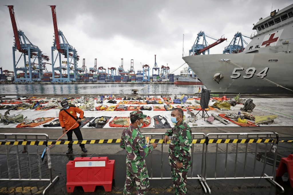 Navy personnel chat as a pieces of the Sriwijaya Air flight SJ-182 retrieved from the Java Sea where the passenger jet crashed on Jan. 9 are laid out ...