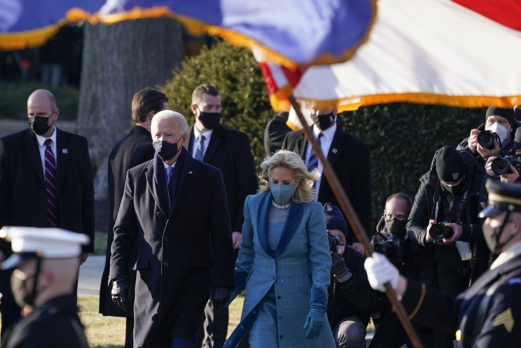 President Joe Biden and first lady Jill Biden walk toward the North Portico of the White House, Wednesday, Jan. 20, 2021, in Washington. (AP Photo/Ale...