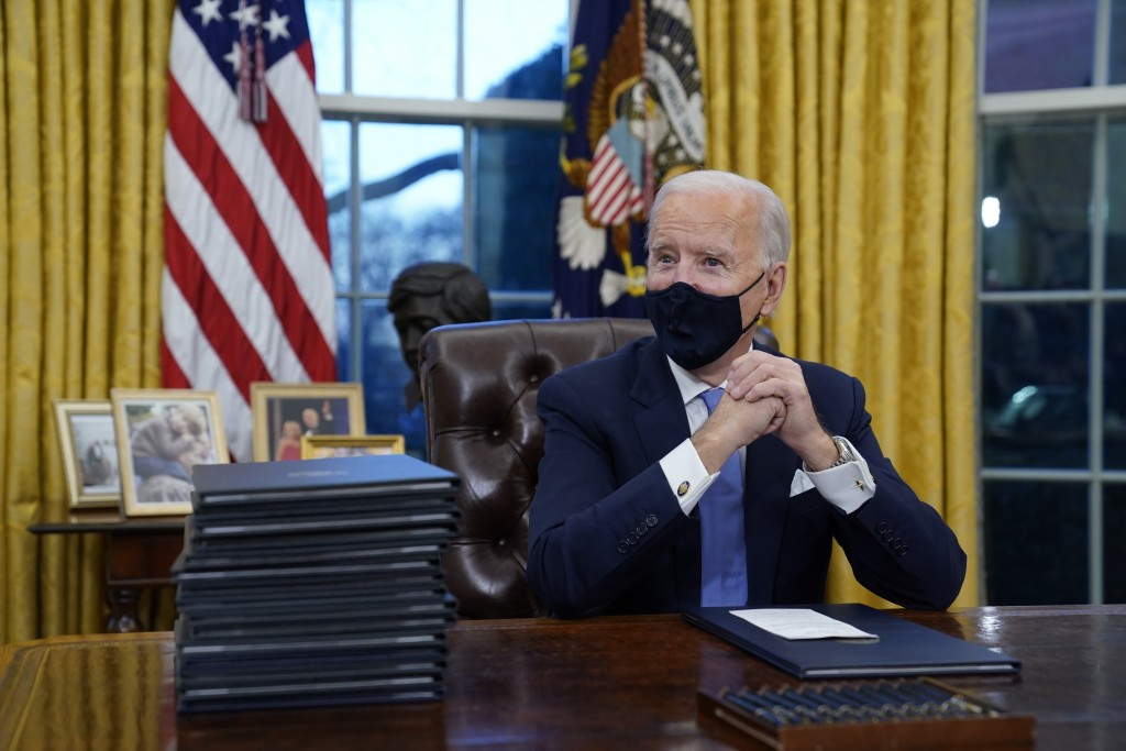 President Joe Biden waits to sign his first executive order in the Oval Office of the White House on Wednesday, Jan. 20, 2021, in Washington.(AP Phot...
