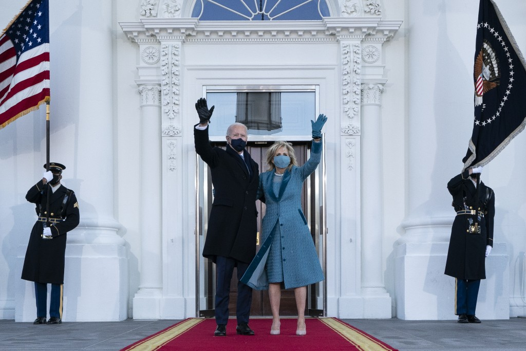 President Joe Biden and first lady Jill Biden wave as they arrive at the North Portico of the White House, Wednesday, Jan. 20, 2021, in Washington. (A...