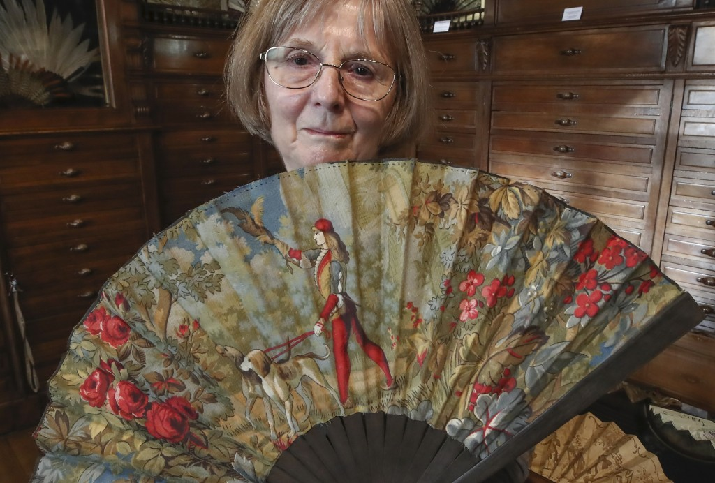 Anne Hoguet, 74, fan maker and director of the hand fan-making museum poses with a wood roasted hand fan representing a falcon hunt, gouache painting ...