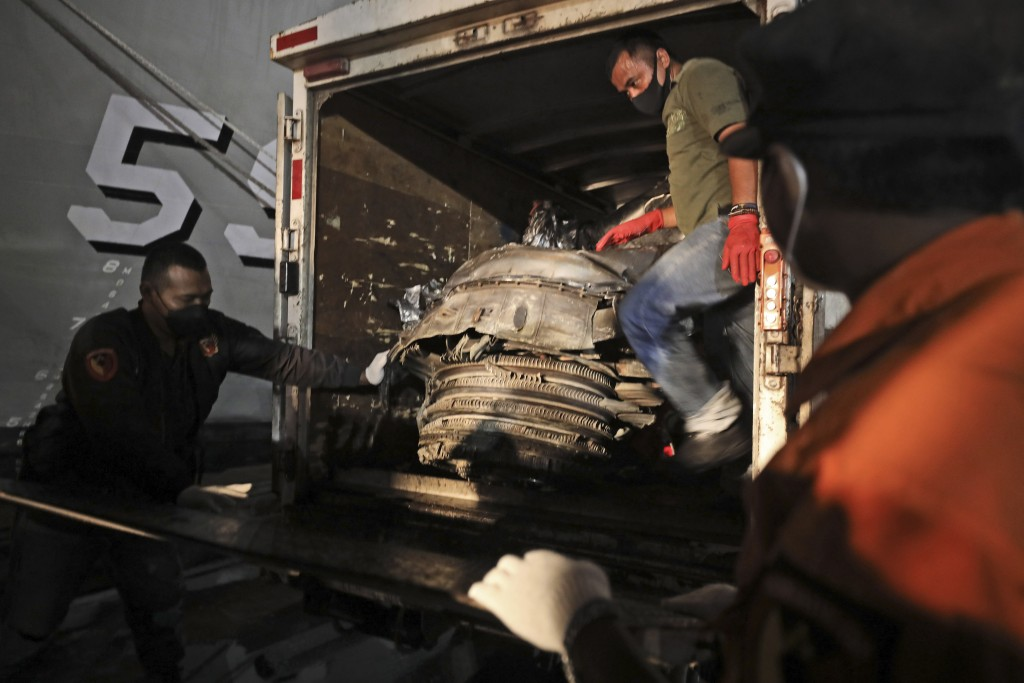 Workers load recovered pieces of Sriwijaya Air flight SJ-182 that crashed into the Java Sea on Jan. 9, onto a truck be transported for further investi...