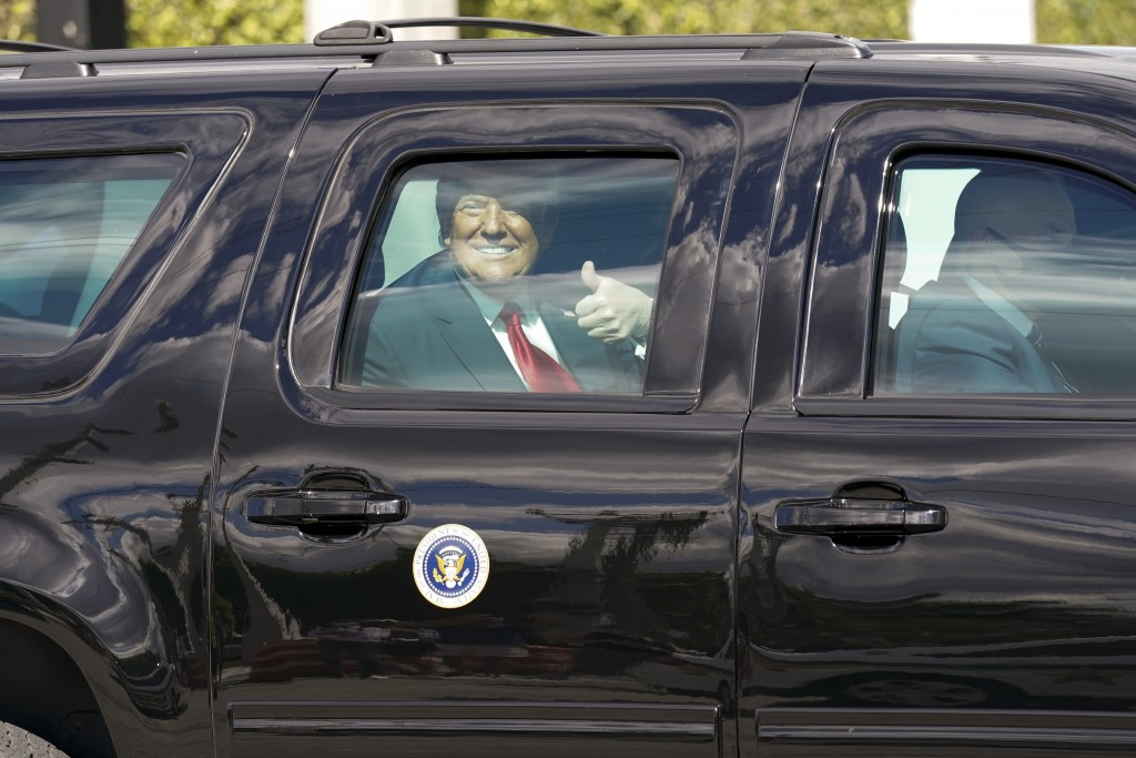 President Donald Trump gestures to supporters en route to his Mar-a-Lago Florida Resort on Wednesday, Jan. 20, 2021, in West Palm Beach, Fla. (AP Phot...