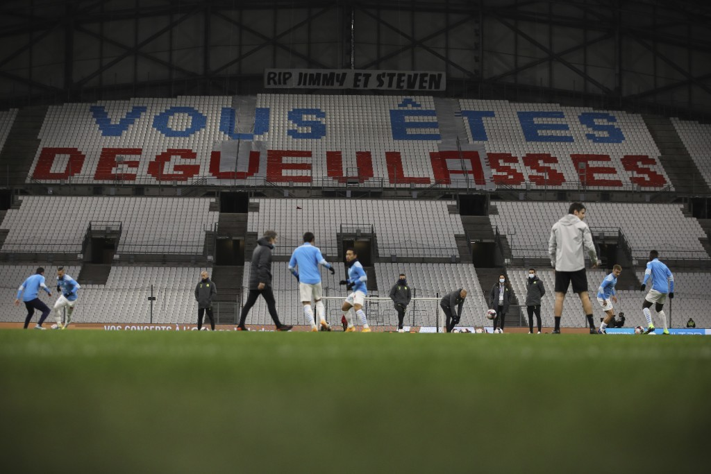 """Marseille players warm up as a tribune decorated by their fans directed at team reads """"You disgust us"""" ahead of the French League One soccer match bet..."""
