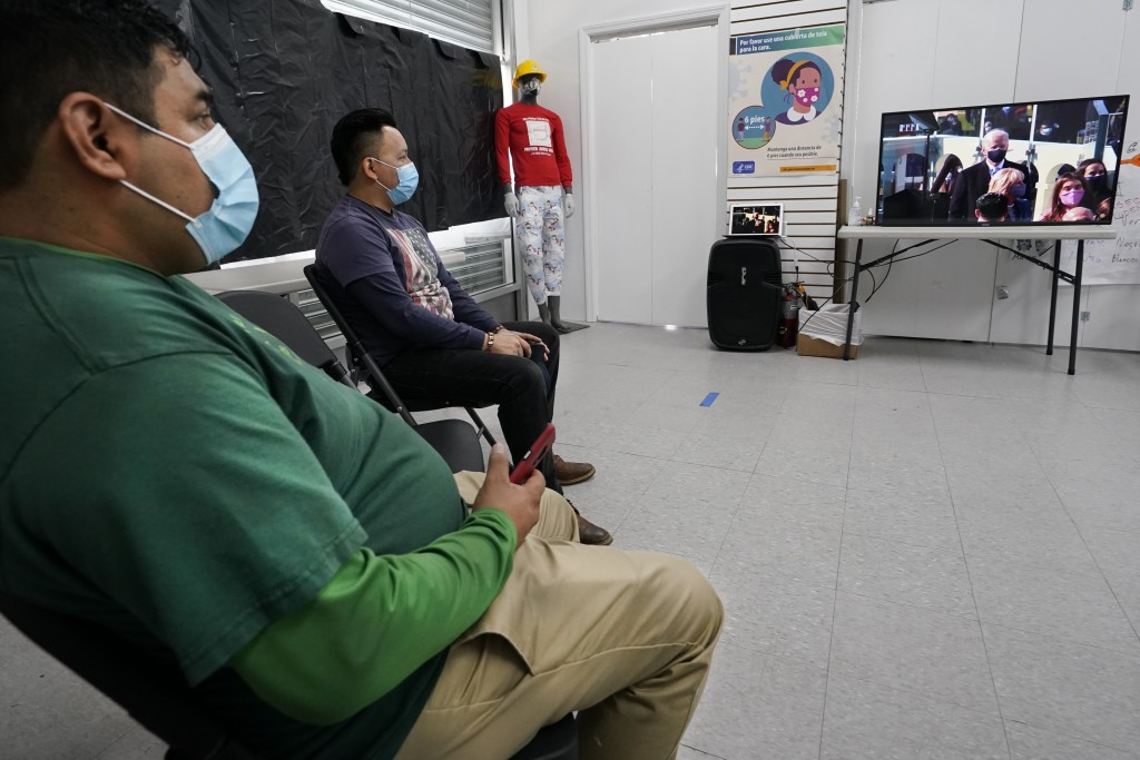 Workers Justice Project Director Gonzalo Cruz, left, and organizer Juan Carlos Romero watch President Joe Biden's presidential inauguration on TV from...