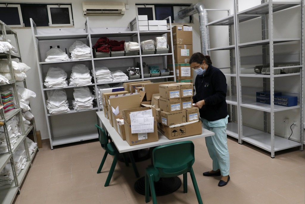 A nurse sorts pharmacy supplies just delivered at a new field hospital set up in a sports hall in Lisbon, Wednesday, Jan. 20, 2021. Portugal's new dai...