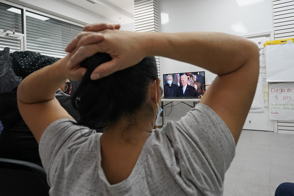Graciela Uraga, a cleaning lady, watches President Joe Biden's inauguration with other immigrants at the Workers Justice Center, Wednesday, Jan. 20, 2...