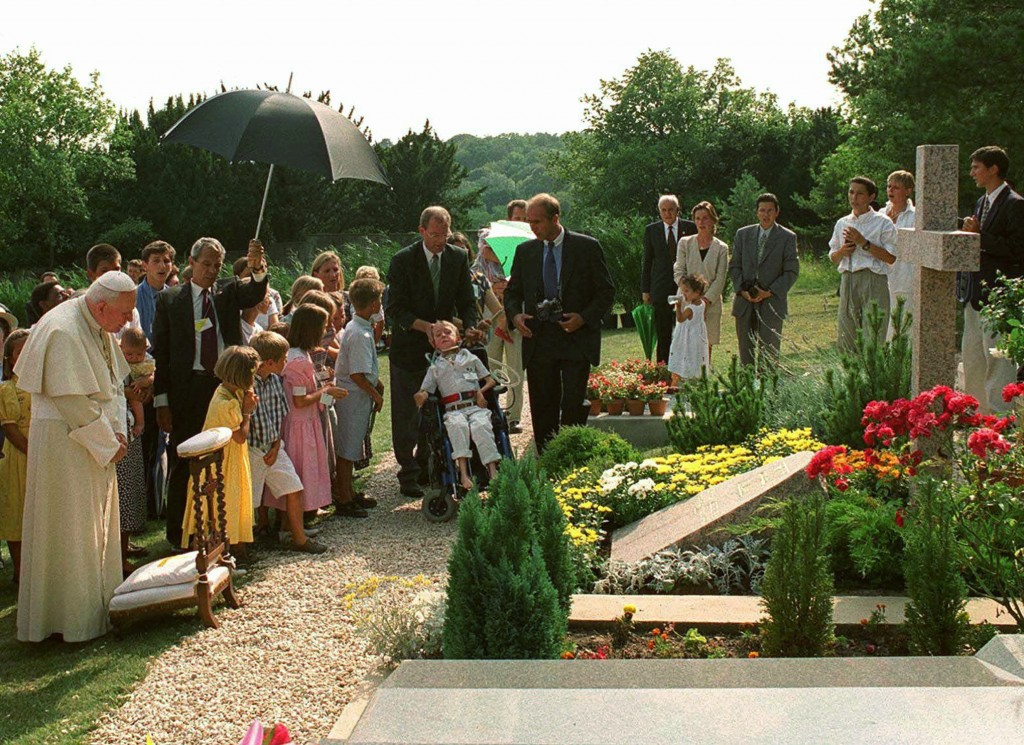 FILE - In this Aug.22, 1997 file photo, Pope John Paul II meditates by the grave of his former friend geneticist Jerome Lejeune, during a private visi...