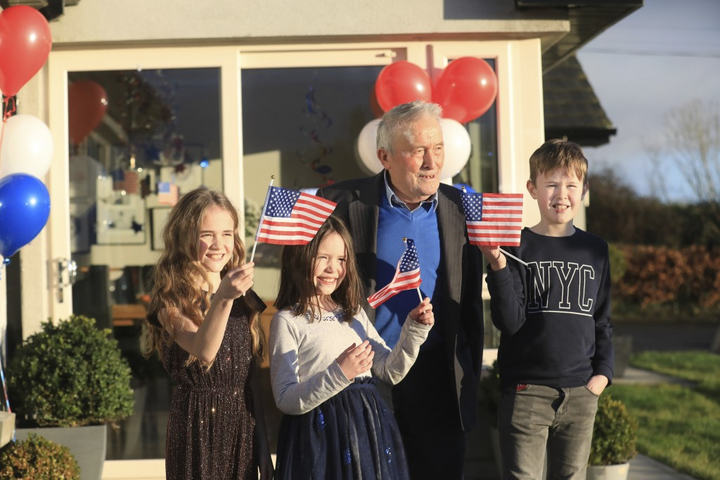 Joe Biden's cousins Brendan Blewitt with his grandchildren Emily, Lauren, and Darragh wave their U.S. flags to the media from their home in Knockmore,...