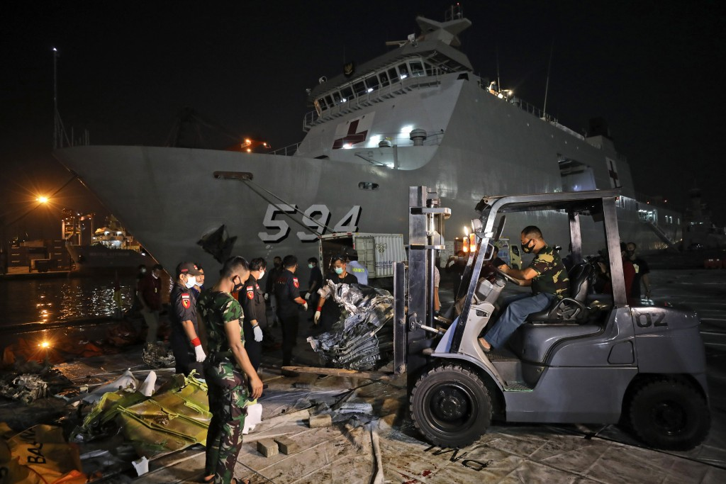 Workers remove parts of the wreckage of Sriwijaya Air flight SJ-182 that crashed into the Java Sea on Jan. 9, to be loaded onto a truck and transporte...