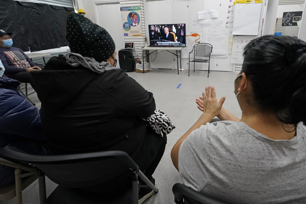 Blanca Cedillos, left, a nanny, and Graciela Uraga, right, a cleaning lady, applaud as they watch the inauguration of President Joe Biden on TV with o...