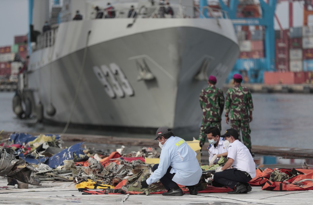 Investigators inspect pieces of the Sriwijaya Air flight SJ-182 retrieved from the Java Sea where the passenger jet crashed on Jan. 9, as an Indonesia...