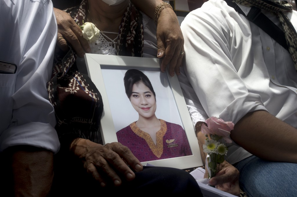 A relative holds a photo of Mia Tresetyani, a victim of the crash of Sriwijaya Air flight SJ-182 during her burial in Denpasar, Bali, Indonesia on Thu...