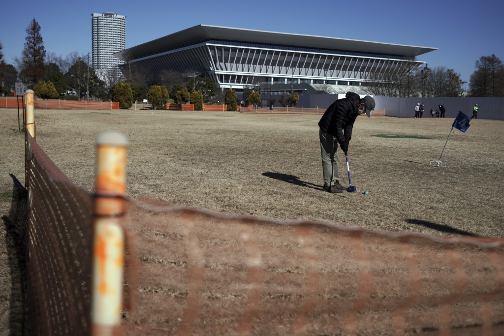 A man wearing a protective mask to help curb the spread of the coronavirus plays ground golf near the Tokyo Aquatics Center, one of the venues of Toky...