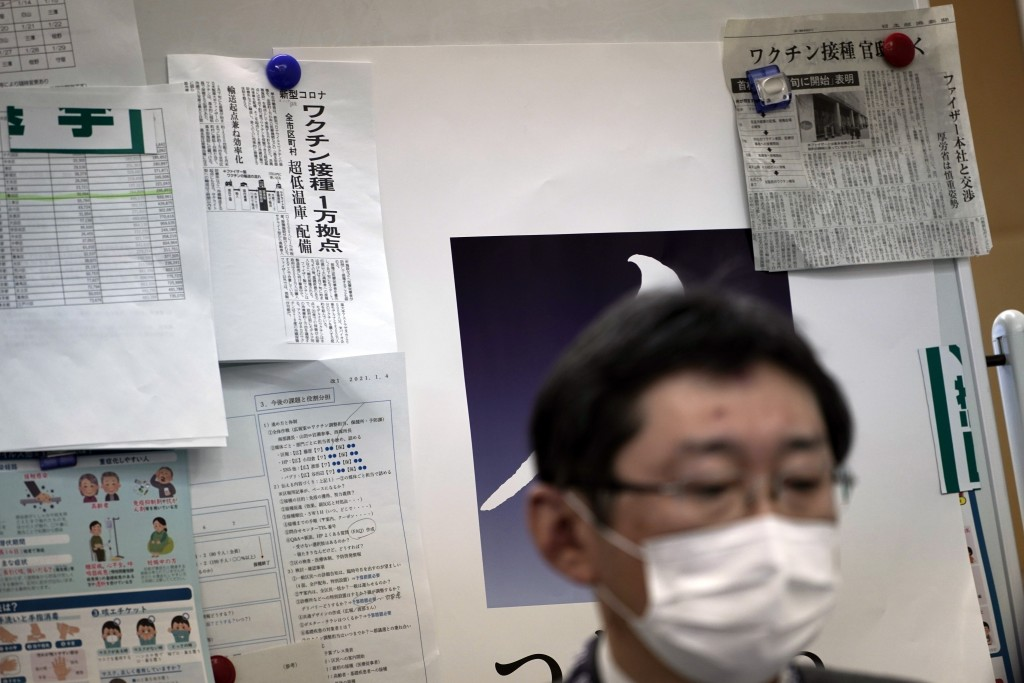 Newspapers' clips on COVID-19 vaccination are posted on a board as Hitoshi Iwase, head of the local office for COVID-19 vaccination preparation at Tok...