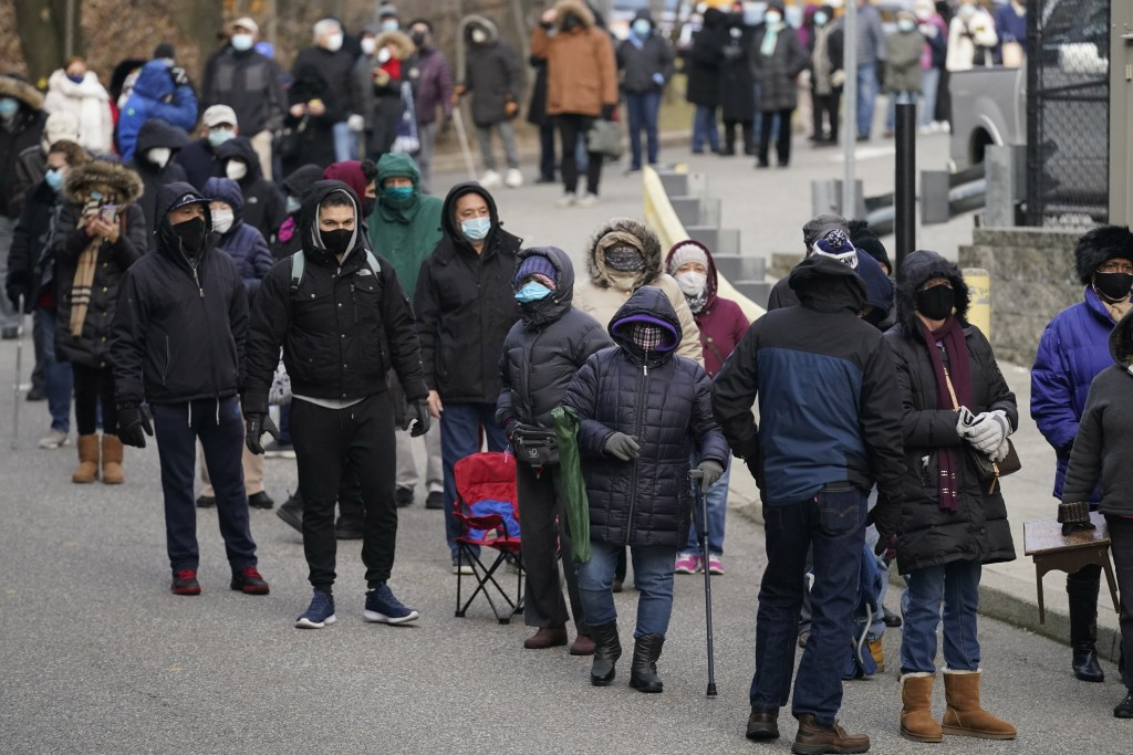 People wait in line for the COVID-19 vaccine in Paterson, N.J., Thursday, Jan. 21, 2021. The first people arrived around 2:30 a.m. for the chance to b...