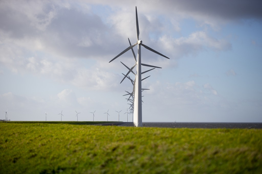 Wind turbines are seen on a dike near Urk, Netherlands, Friday, Jan. 22, 2021. A group of scientists, including five Nobel laureates, called Friday fo...