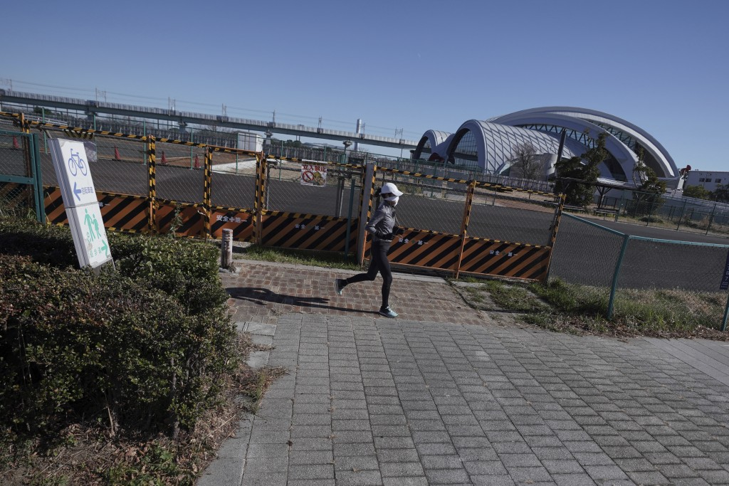 A woman runs near Tokyo Tatsumi International Swimming Center, one of the venues of Tokyo 2020 Olympic and Paralympic games, in Tokyo Wednesday, Jan. ...
