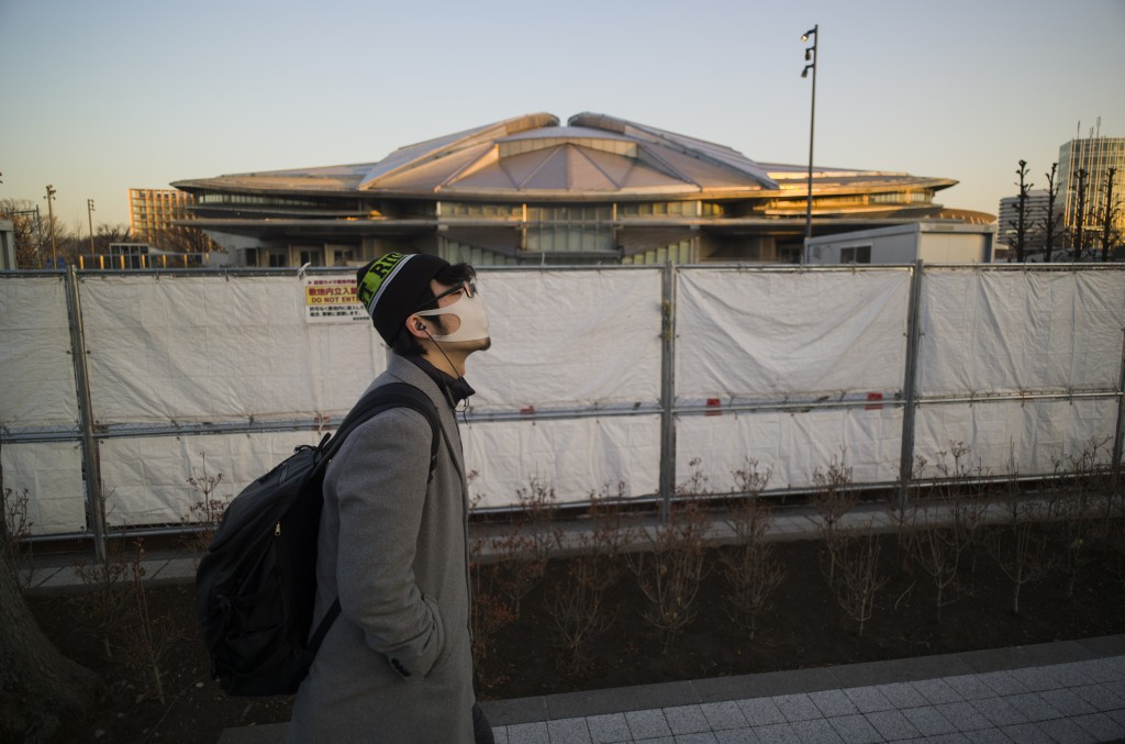 A man walks past the closed Tokyo Metropolitan Gymnasium, a venue renovated to be used in the rescheduled Tokyo Olympics, in Tokyo on Thursday, Jan. 2...