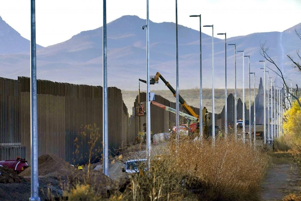 FILE - Crews construct a section of border wall in San Bernardino National Wildlife Refuge, Tuesday, Dec. 8, 2020, in Douglas, Ariz. President Biden o...
