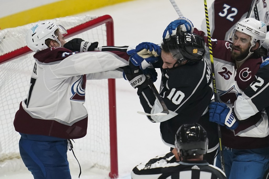 Colorado Avalanche left wing J.T. Compher, left, and Los Angeles Kings center Michael Amadio (10) fight during the first period of an NHL hockey game ...