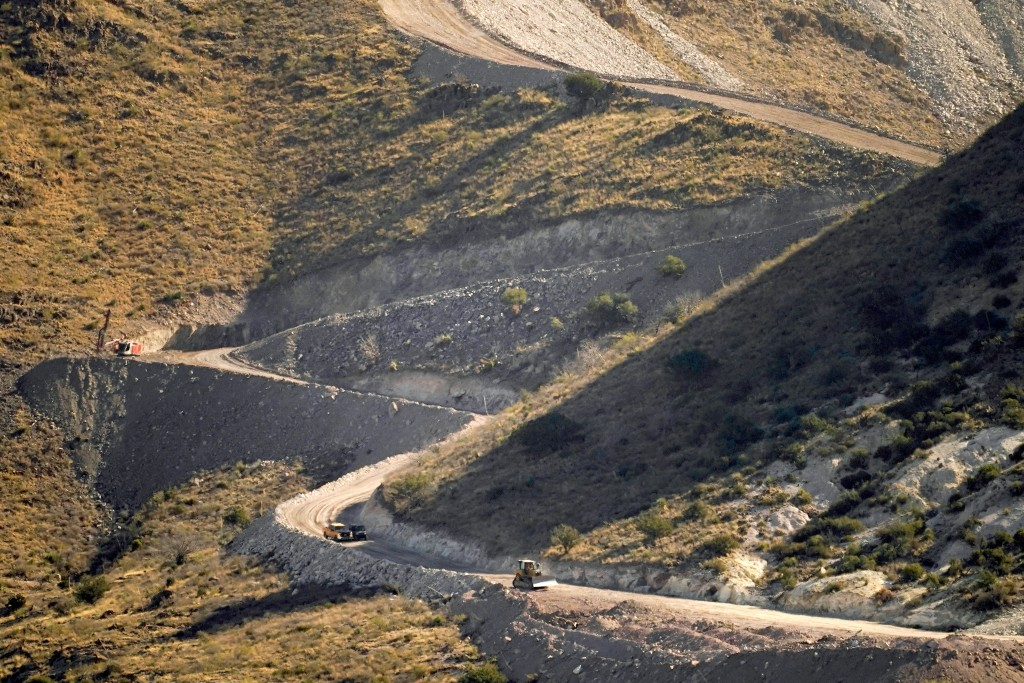 FILE - A pathway cleared by explosives to make way for border wall construction separates Mexico, right, and the United States, Wednesday, Dec. 9, 202...