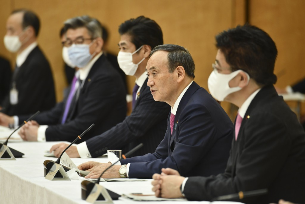 Japanese Prime Minister Yoshihide Suga, second from right, speaks during a meeting of the coronavirus infection control headquarters at his office in ...