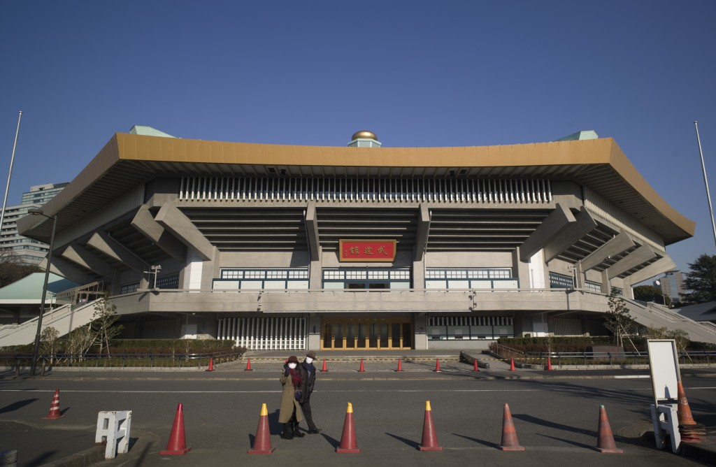 A man and a woman walk past the Nippon Budokan arena, one of the venues planned to be used in the rescheduled Tokyo Olympics, in Tokyo on Thursday, Ja...